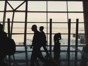 Silhouettes of people walking through airport terminal.