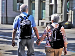 A senior couple holding hands and walking with backpacks.